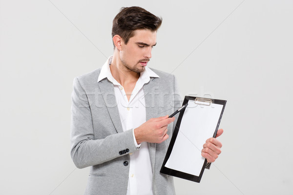 Handsome man pointing on clipboard Stock photo © deandrobot
