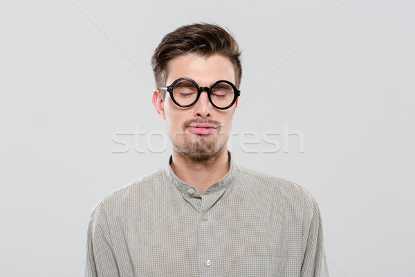 Young guy with closed eyes in black round glasses Stock photo © deandrobot