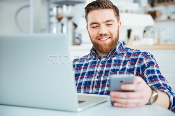 Man using smartphone and laptop compute in cafe Stock photo © deandrobot