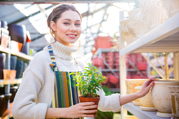 Cheerful cute young female gardener standing and choosing new pot  Stock photo © deandrobot
