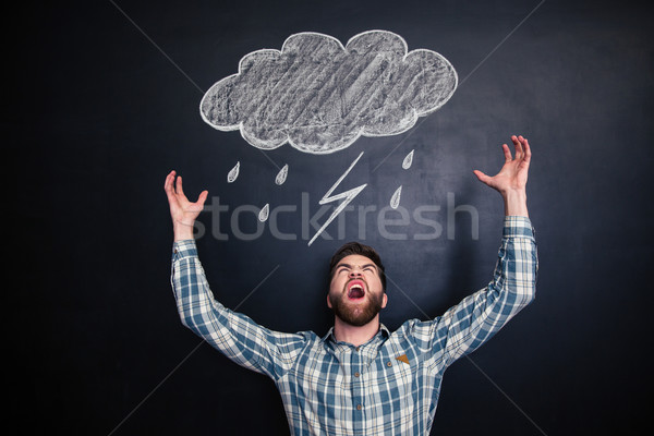 Stock photo: Angry man standing and shouting over blackboard with drawn raincloud