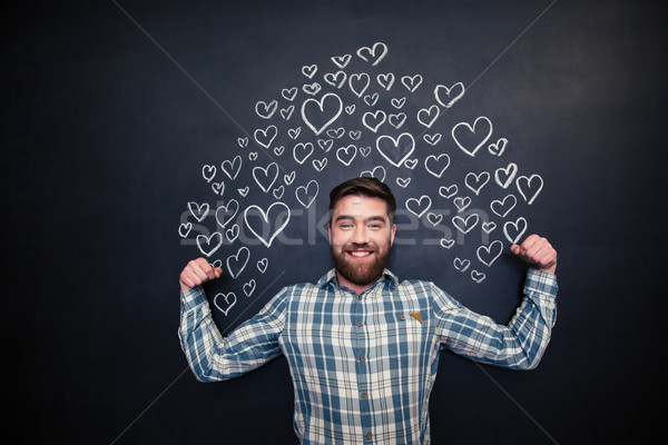 Happy man showing biceps and standing on blackboard background Stock photo © deandrobot