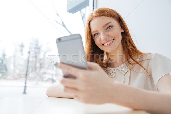 Cheerful woman with long red hair using smartphone in cafe  Stock photo © deandrobot