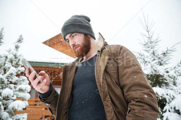 Serious man using smartphone standing outdoors in winter Stock photo © deandrobot