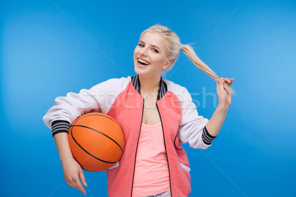Cheerful female student holding basketball ball Stock photo © deandrobot