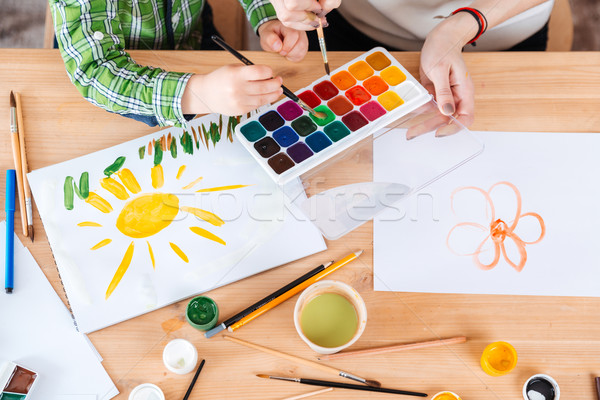 Hands of mother and little son using watercolor paints together Stock photo © deandrobot