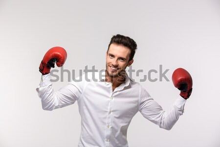 Amazed comical man boxer in red gloves showing his biceps Stock photo © deandrobot