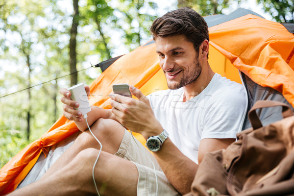 Man tourist charging battery of mobile phone in touristic tent Stock photo © deandrobot