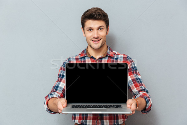 Smiling young man in checkered shirt holding blank screen laptop Stock photo © deandrobot