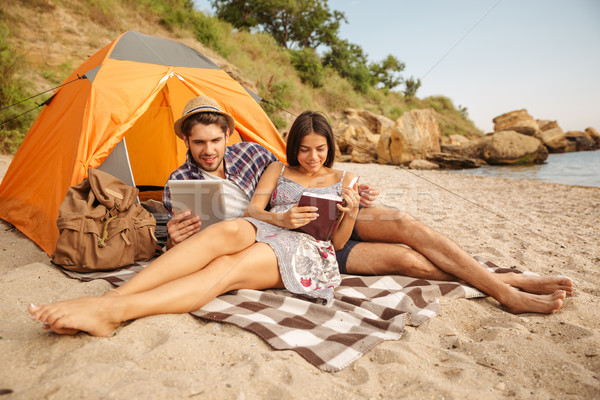 Couple sitting at tent using tablet computer and reading book Stock photo © deandrobot