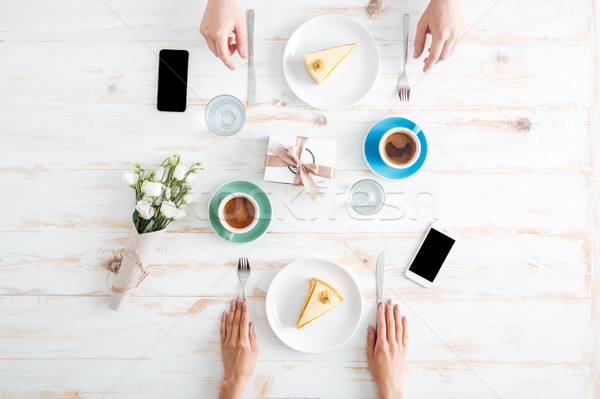 Hands of couple eating cakes and drinking coffee on table Stock photo © deandrobot