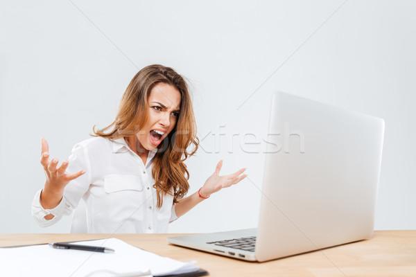 Folle furieux jeunes femme d'affaires utilisant un ordinateur portable hurlant Photo stock © deandrobot