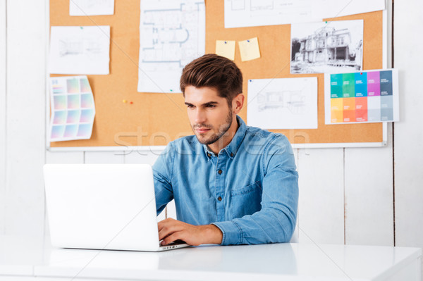 Handsome bearded casual businessman sitting with laptop at office Stock photo © deandrobot