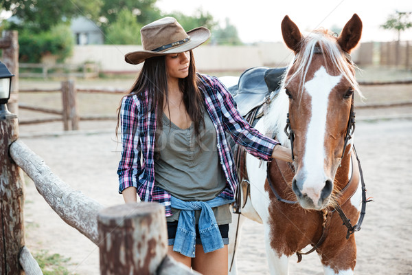 Woman cowgirl walking with her horse on ranch Stock photo © deandrobot