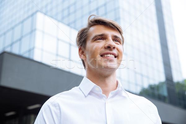 Wesoły biznesmen stałego nowoczesne wieżowiec udany Zdjęcia stock © deandrobot
