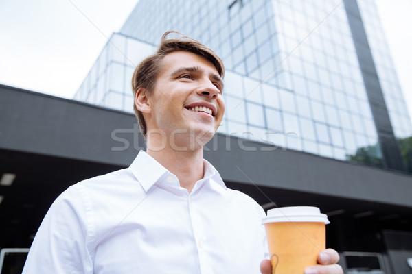 Gelukkig zakenman permanente wolkenkrabber drinken koffie Stockfoto © deandrobot