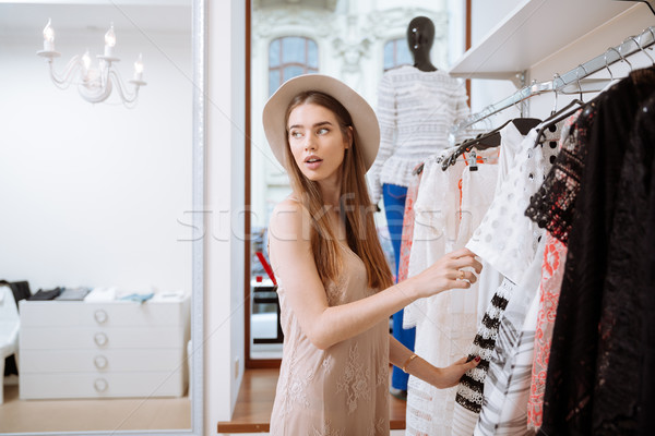 Pretty woman choosing clothes and doing shopping in clothing shop Stock photo © deandrobot