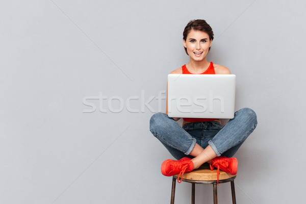 Young beautiful smiling girl using laptop pc computer for study Stock photo © deandrobot