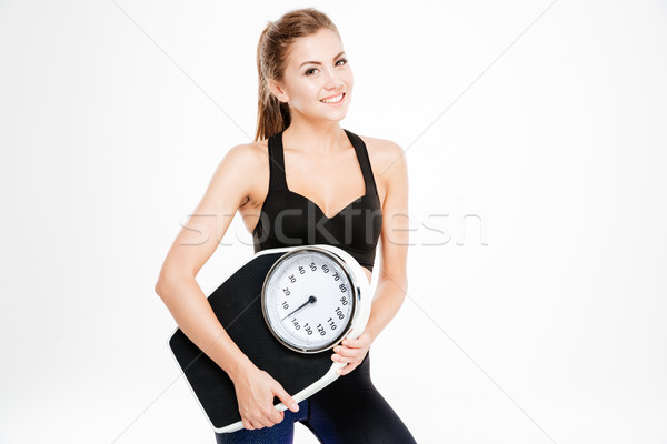 Happy fitness woman holding weighing machine Stock photo © deandrobot