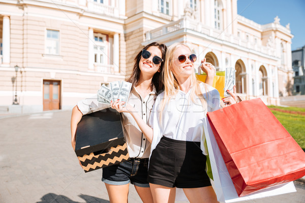 Two attractive young women holding shopping bags and smiling Stock photo © deandrobot