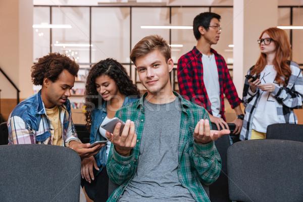 Confusi giovane cellulare amici parlando sorridere Foto d'archivio © deandrobot