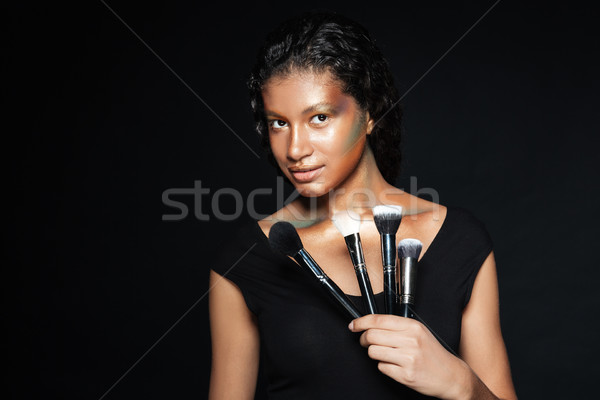 Beautiful african american young woman holding makeup brushes Stock photo © deandrobot