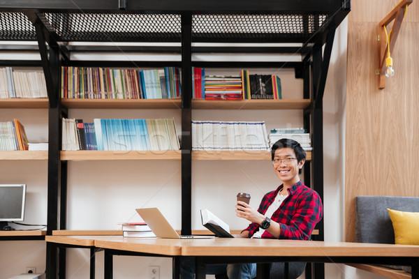 Stock fotó: Férfi · laptopot · használ · olvas · könyv · iszik · kávé