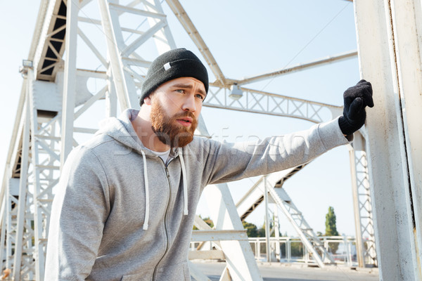Portrait of a man athlete having break after workout outdoors Stock photo © deandrobot