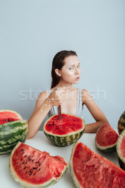 Portrait of serious young woman sitting and cutting watermelon Stock photo © deandrobot