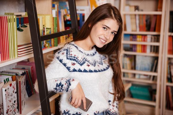 Vrouw permanente boekenplank mobiele telefoon glimlachend jonge vrouw Stockfoto © deandrobot