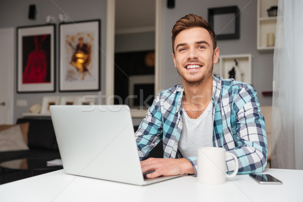 Cheerful young man using laptop computer Stock photo © deandrobot