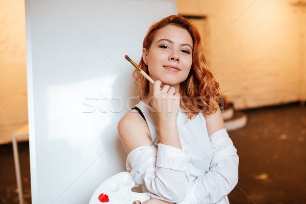 Beautiful woman painter standing over blank canvas in artist workshop Stock photo © deandrobot