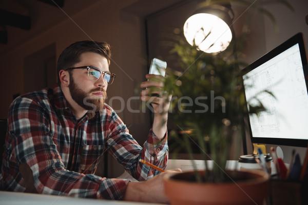 Portret jonge geconcentreerde aantrekkelijk man mobiele telefoon Stockfoto © deandrobot