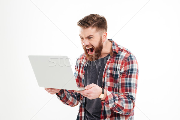 Angry man in plaid shirt screaming at laptop in hands Stock photo © deandrobot
