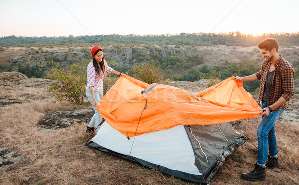 Happy young couple setting a tent outdoors Stock photo © deandrobot