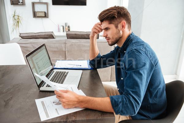 Geconcentreerde man met behulp van laptop naar papieren foto Stockfoto © deandrobot