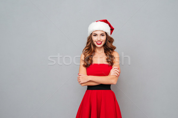 Woman in santa's hat and dress with arms crossed Stock photo © deandrobot