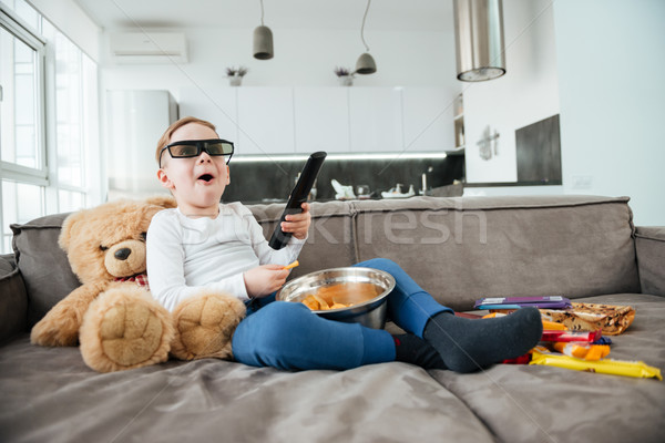 Little boy on sofa with teddy bear watching TV Stock photo © deandrobot