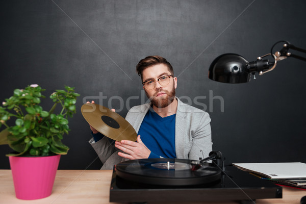 Handsome businessman in glasses with turntable and golden vinyl record Stock photo © deandrobot