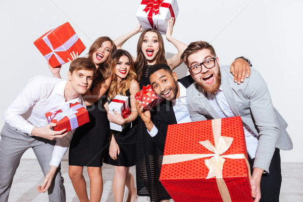 Happy funny young people holding gift boxes and having fun Stock photo © deandrobot