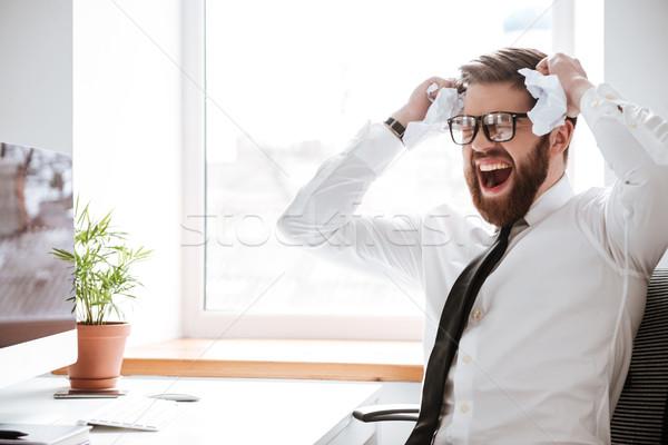 Sikít üzletember ül iroda tart papír Stock fotó © deandrobot