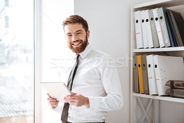 Boldog fiatal üzletember tart tabletta néz Stock fotó © deandrobot