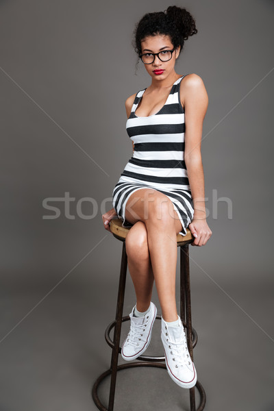 Beautiful african american young woman sitting and posing on chair Stock photo © deandrobot