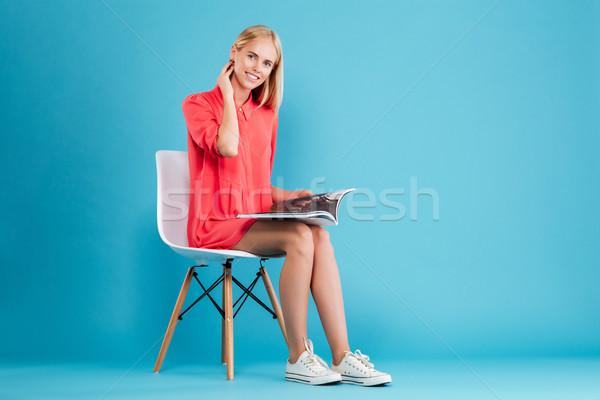 örömteli szőke nő ül szék kinyitott magazin Stock fotó © deandrobot