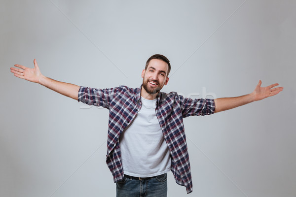 Bearded man in shirt with hands to the sides Stock photo © deandrobot