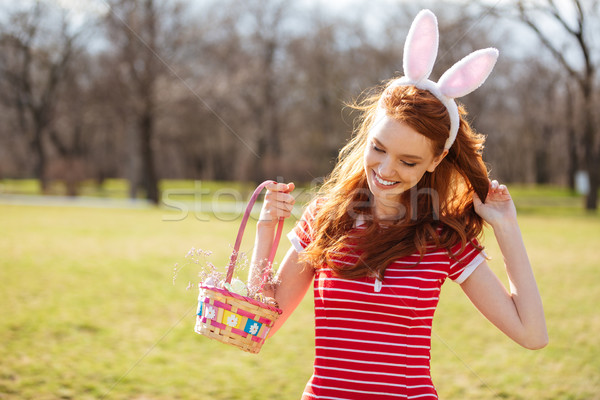 Woman with long red hair holding basket with painted eggs Stock photo © deandrobot