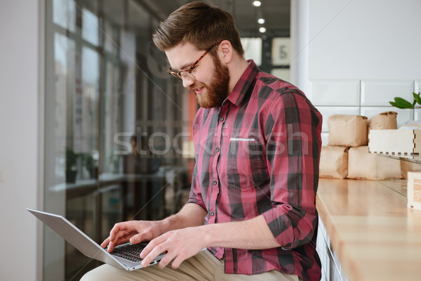 Smiling young man in eyeglasses sitting in cafe Stock photo © deandrobot