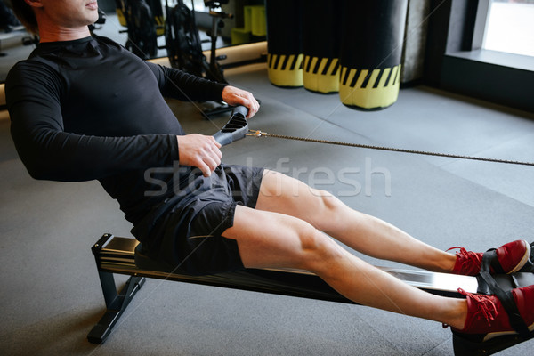 Side view of Muscular man using rowing machine Stock photo © deandrobot