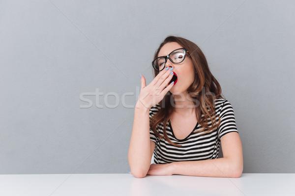 Genç bayan gözlük oturma Stok fotoğraf © deandrobot