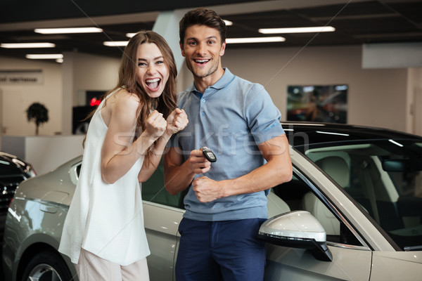 Lovng couple standing near car in car dealership. Stock photo © deandrobot
